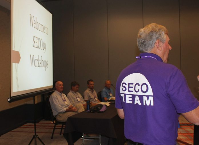 A presenter at SECO19 standing in front of a panel of speakers